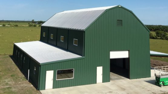 Big green gambrel metal barn with one fully enclosed leanto and one open leanto.