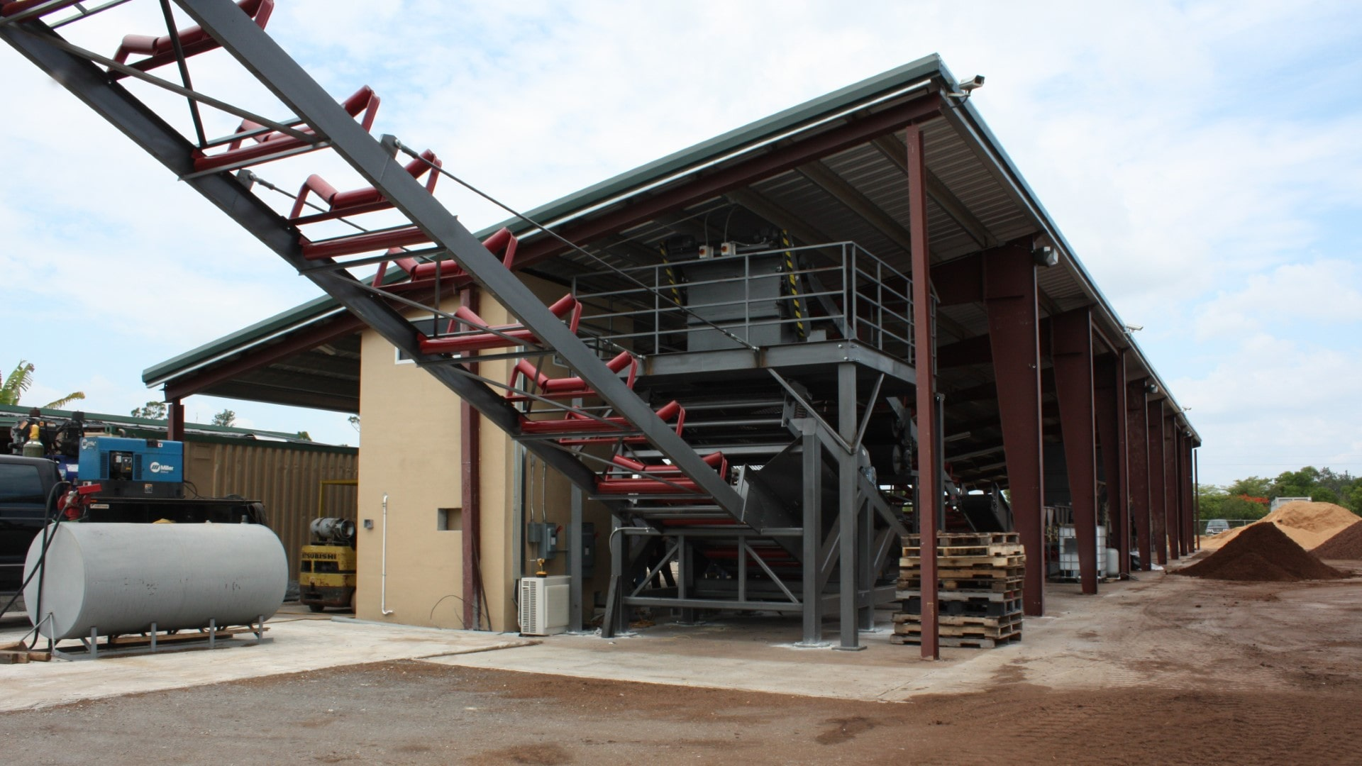 Single slope open roof only metal building protecting commercial composting machinery.