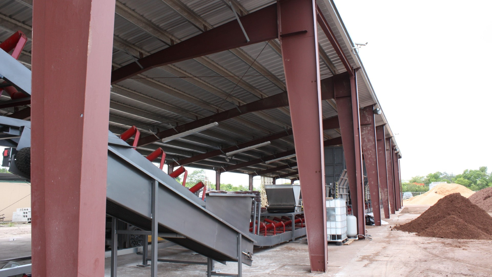 Single slope open roof only metal building view of columns and protected composting equipment.
