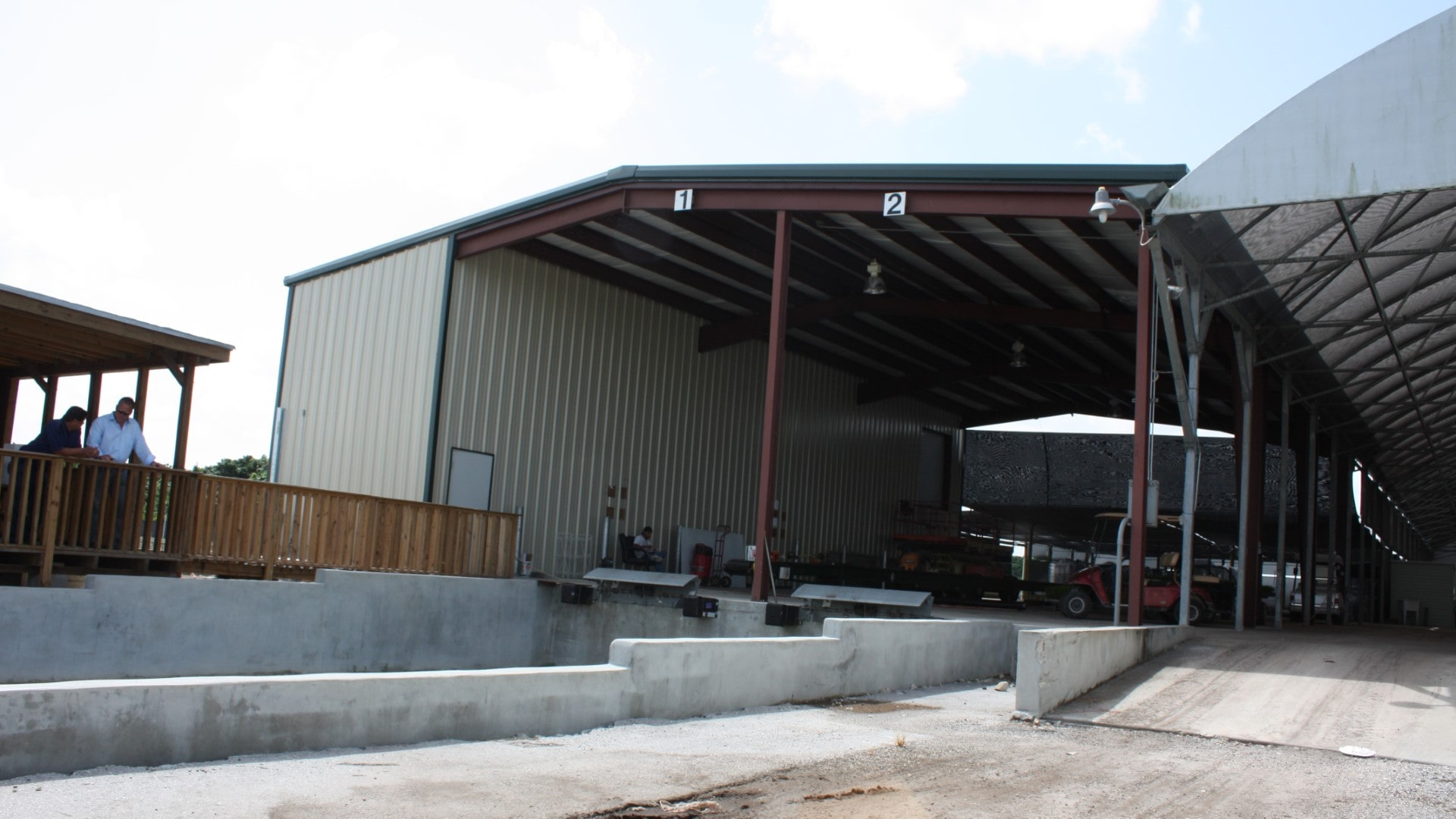Partially open steel agricultural building with loading dock on gable end.