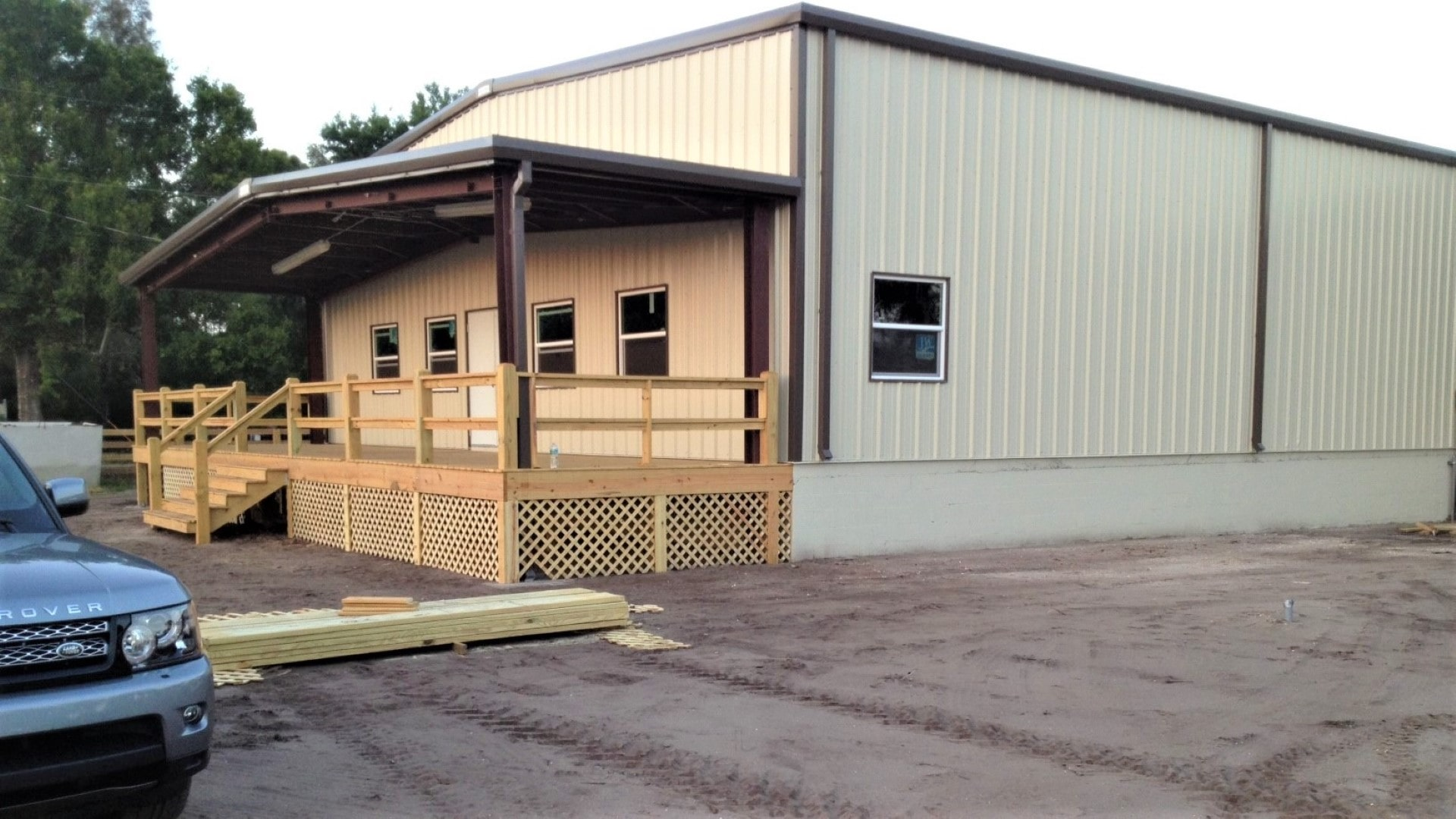 Saddle tan metal building with brown trim, covered entrance to offices on gable end and covered loading dock on sidewall.