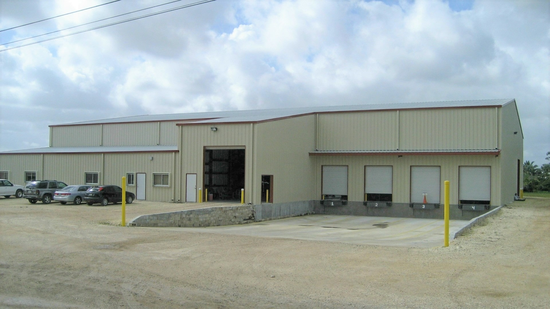 Commercial plant grower packing house tan steel building with loading dock view from front sidewall.