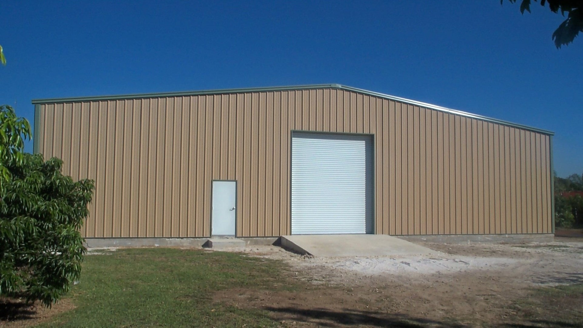 Steel farm storage building in brown color with green trim and white doors.