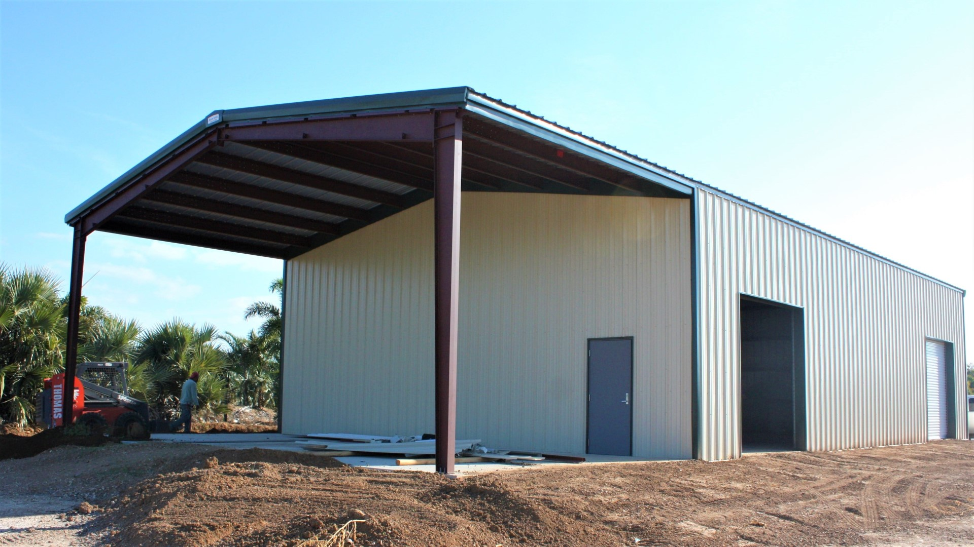 Farm steel storage building with inset bay, tan color with green trim.