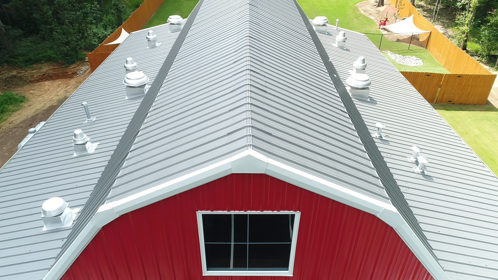 Red gambrel steel barn with 2 leantos view from end wall looking down gambrel roofline.