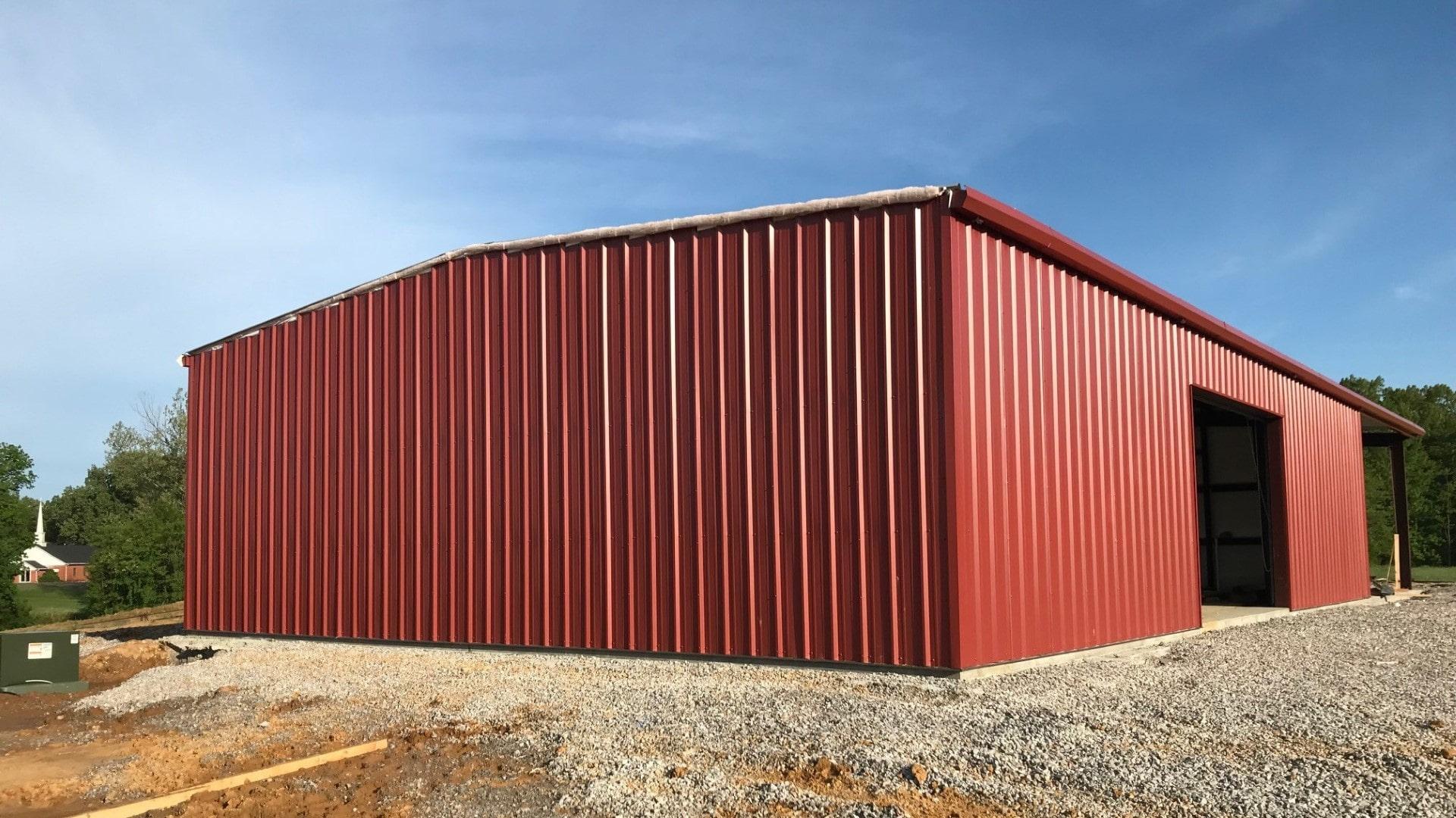 Red metal garage kit view of gable end during erecting awaiting rake trim installation.