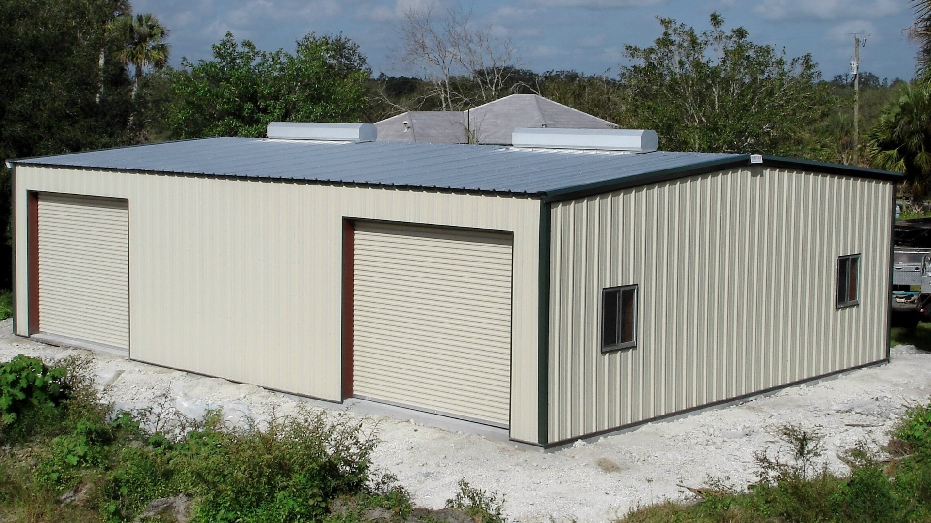 Tan metal garage kit with color-matched commercial rollup doors, windows and ridge vents.