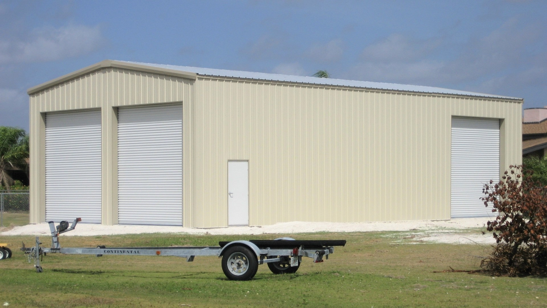 Tan RV and boat storage steel building with 2 rollup doors on gable end and 1 rollup door on front sidewall.