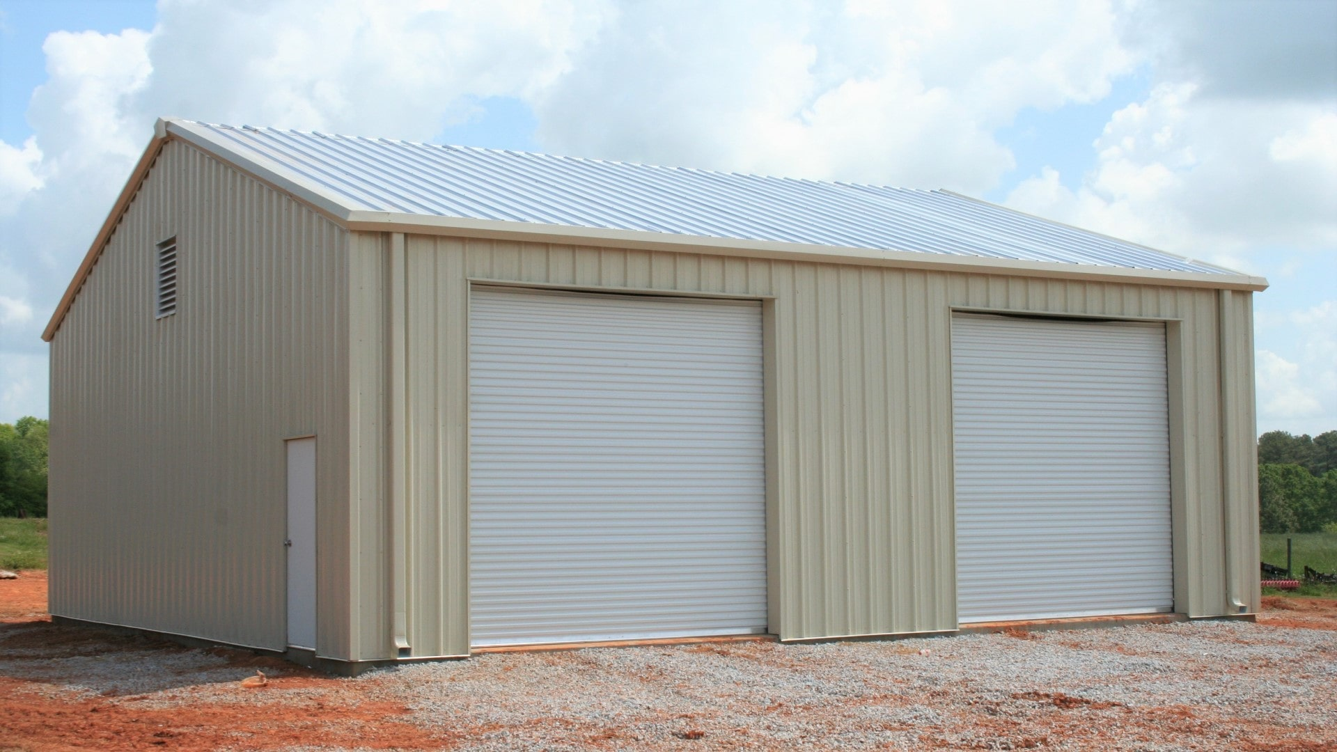 Tan metal garage with tan trim, rollup doors, walk door, and louver vent. View from front sidewall.