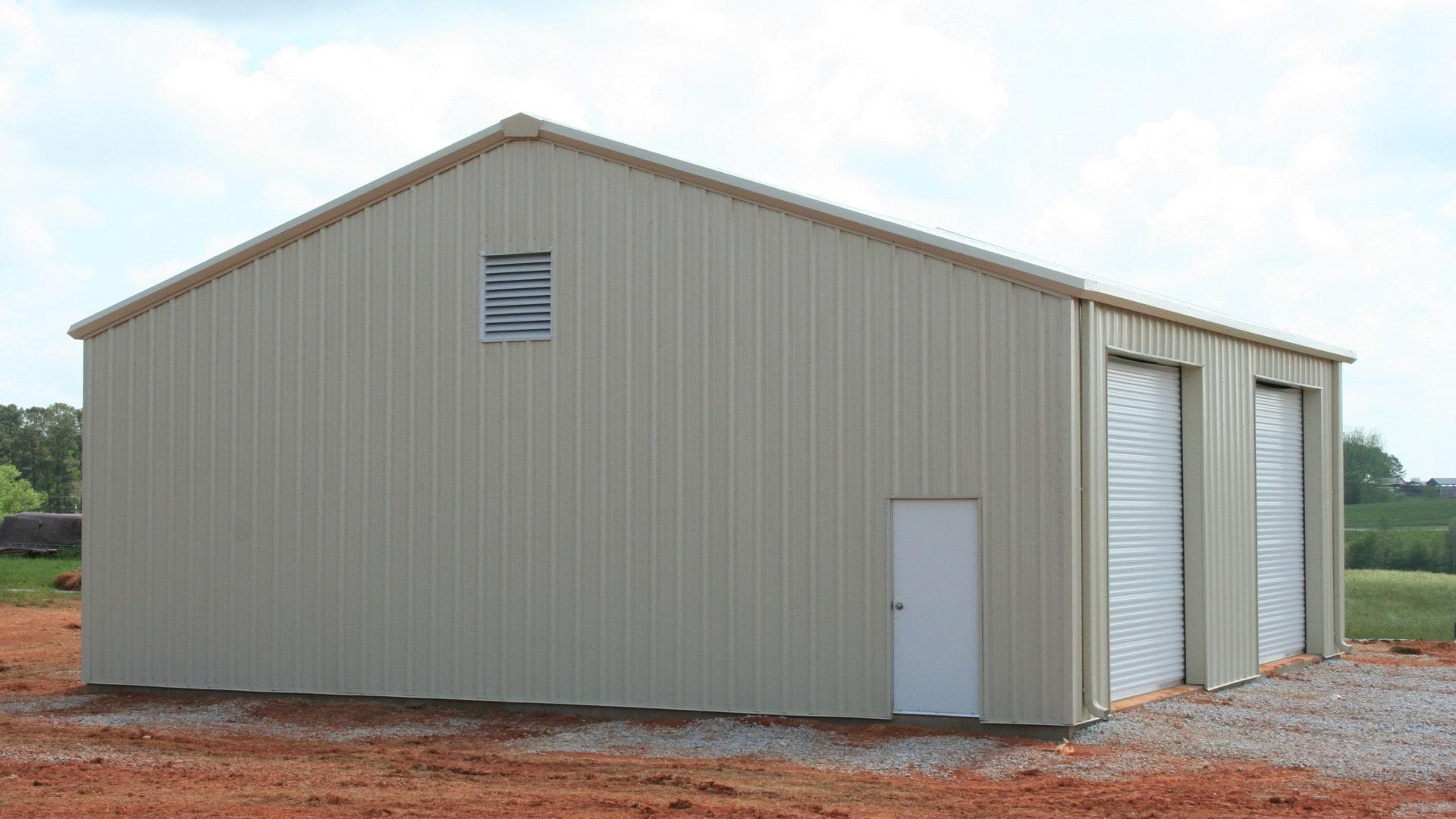 Tan metal garage with tan trim, rollup doors, walk door, and louver vent. View from left endwall.