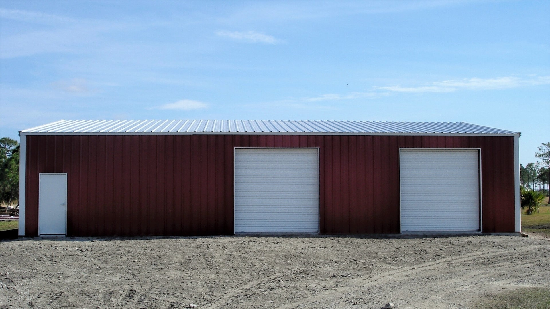 Red metal building with white trim, walk door, and 3 rollup doors. View of front sidewall.