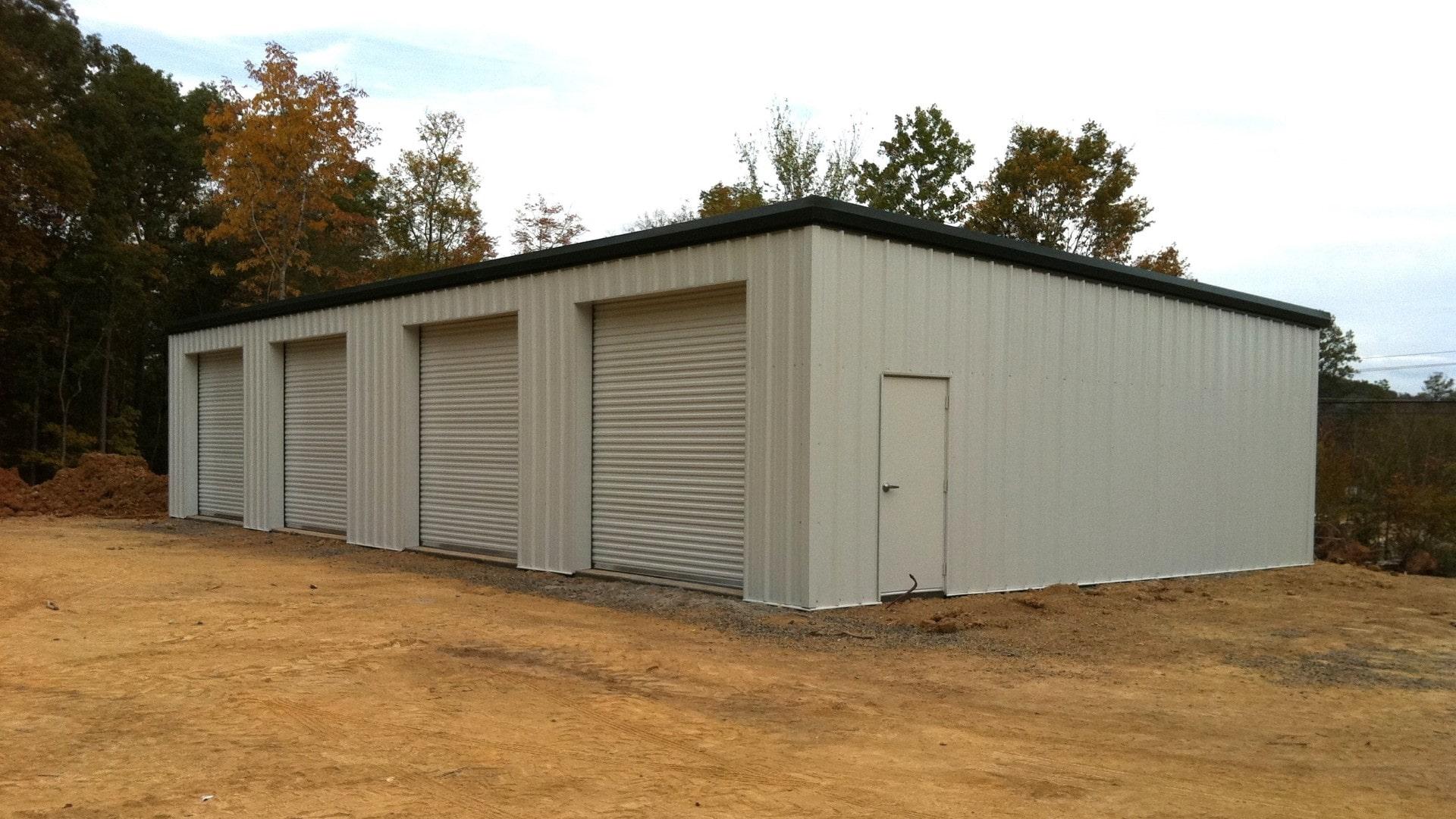 Tan single slope metal garage with dark green trim, walk door, and 4 rollup doors. View of front sidewall left endwall corner.