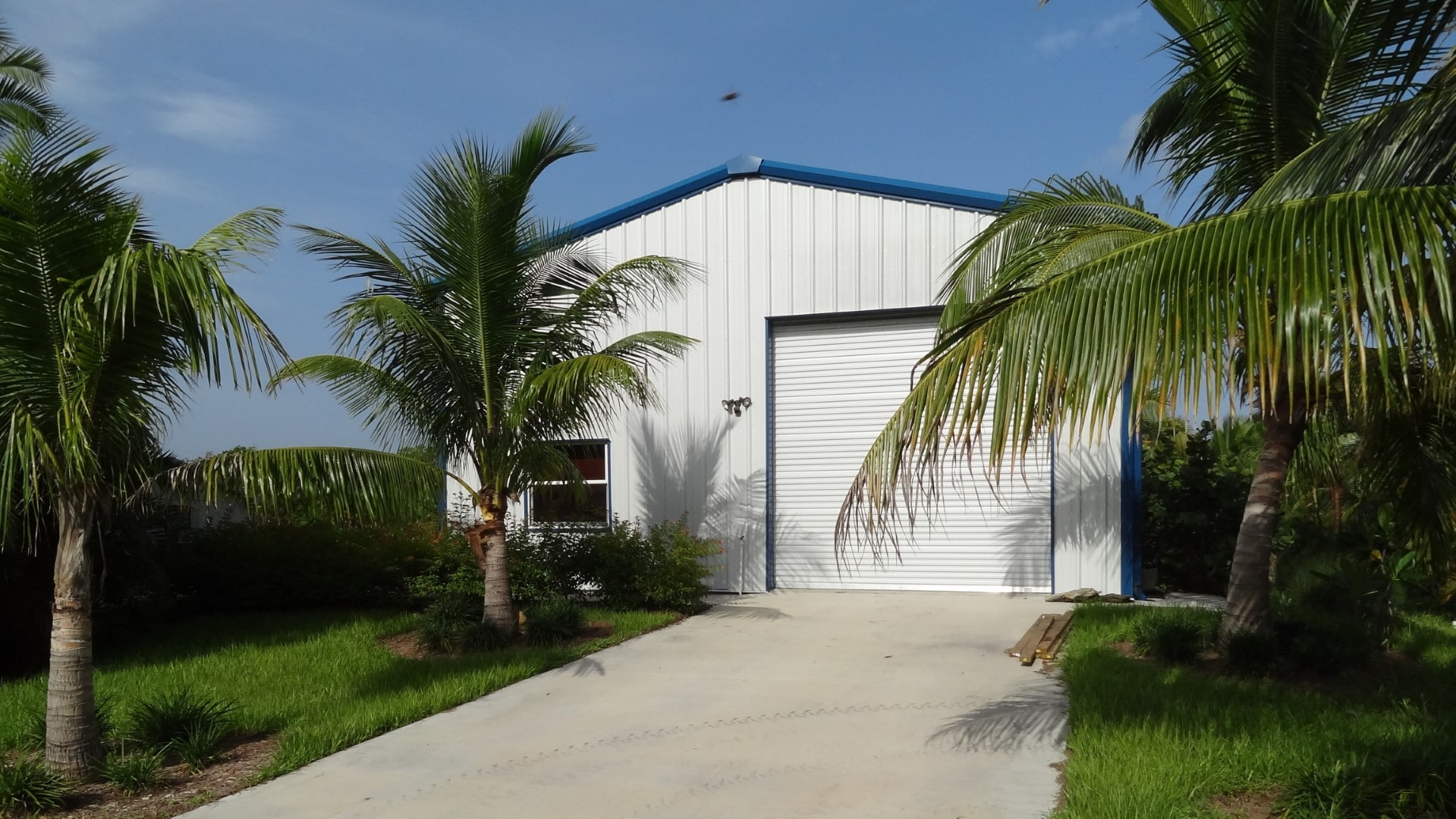 White metal garage with blue trim, rollup door and window.
