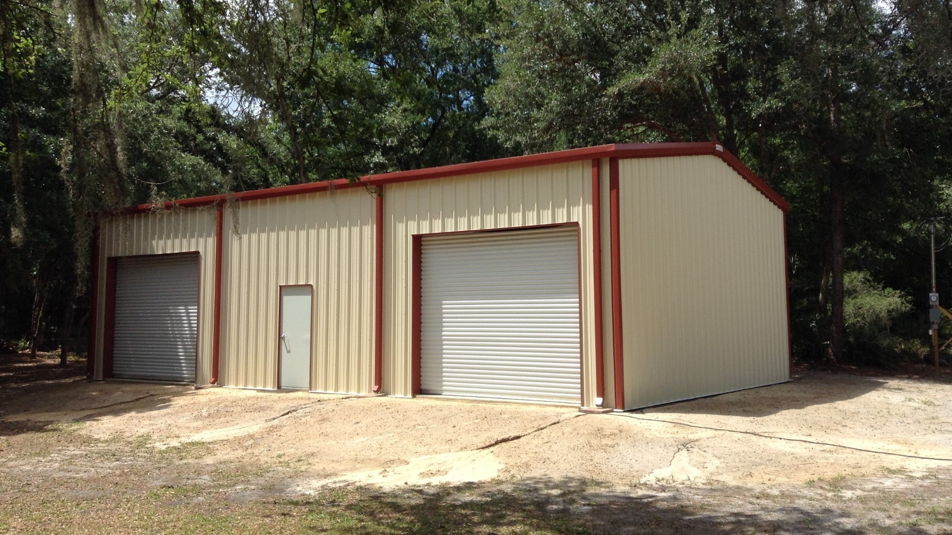 Tan metal garage kit with red trim, walk door in center of front sidewall with rollup door on each side.