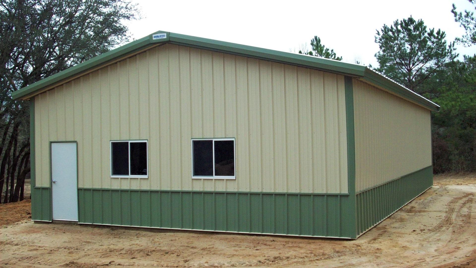 Tan metal garage with green trim, green wainscoting, walk door and windows. View of right endwall.