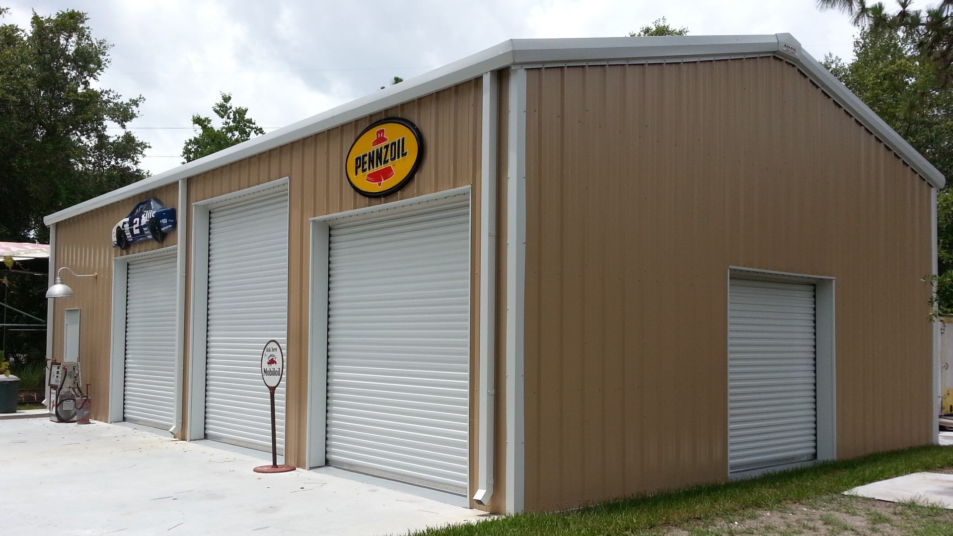 Tan metal garage kit with white roof and trim, walk door, and 4 rollup doors. View of front sidwall and right endwall.