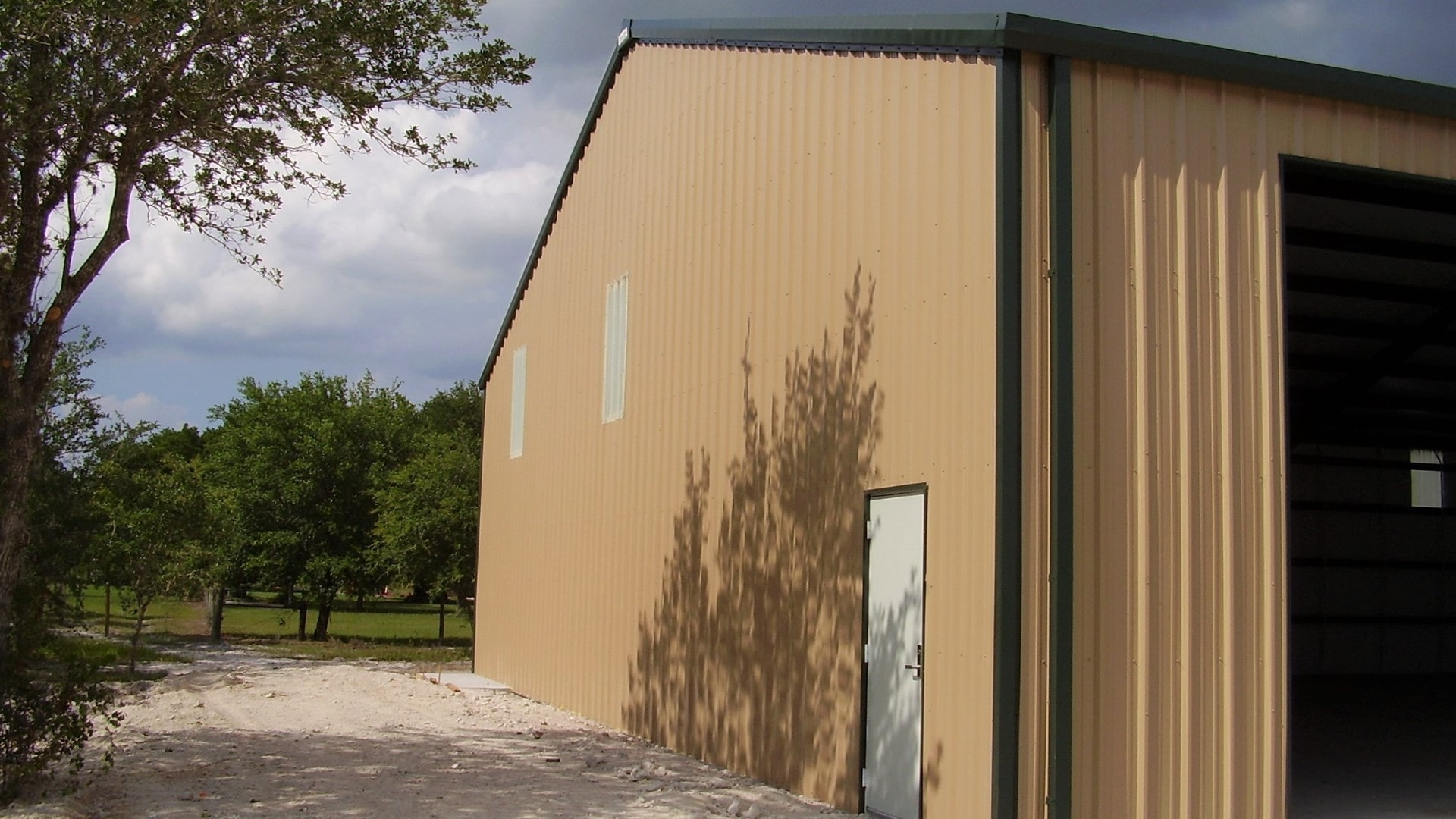 Tan steel building with dark roof and trim, 3 large rollup doors and wall LTPs. View of left endwall.