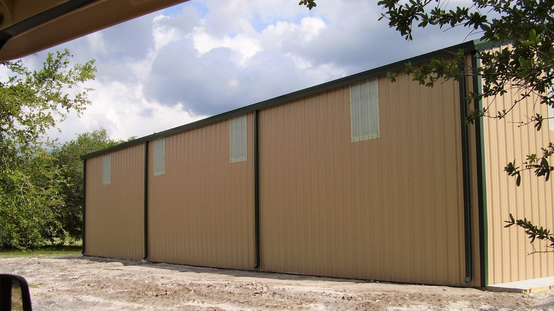 Tan steel building with dark roof and trim, 3 large rollup doors and wall LTPs. View of back sidewall.