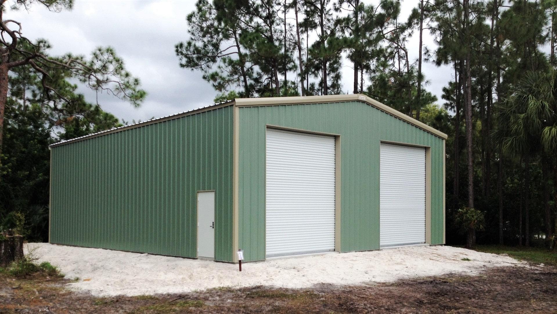 Green metal garage kit with tan trim, walk door, and 2 rollup doors.