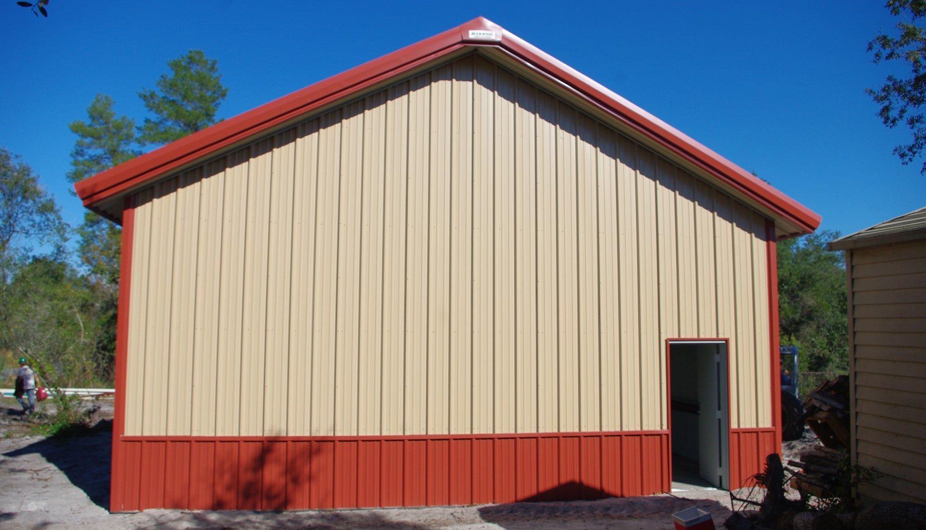 Tan metal building kit with red trim, red wainscoting, and roof extensions with soffit.