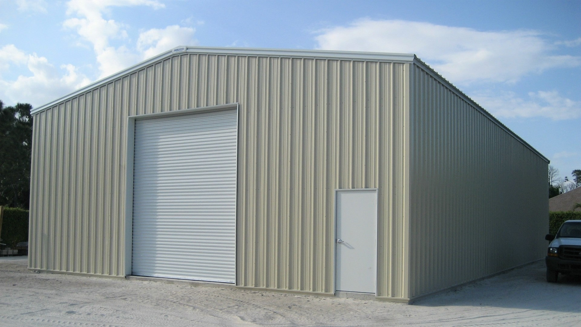 Tan metal garage shop with white trim, white walk door and white rollup door. View of right endwall and back  sidewall.