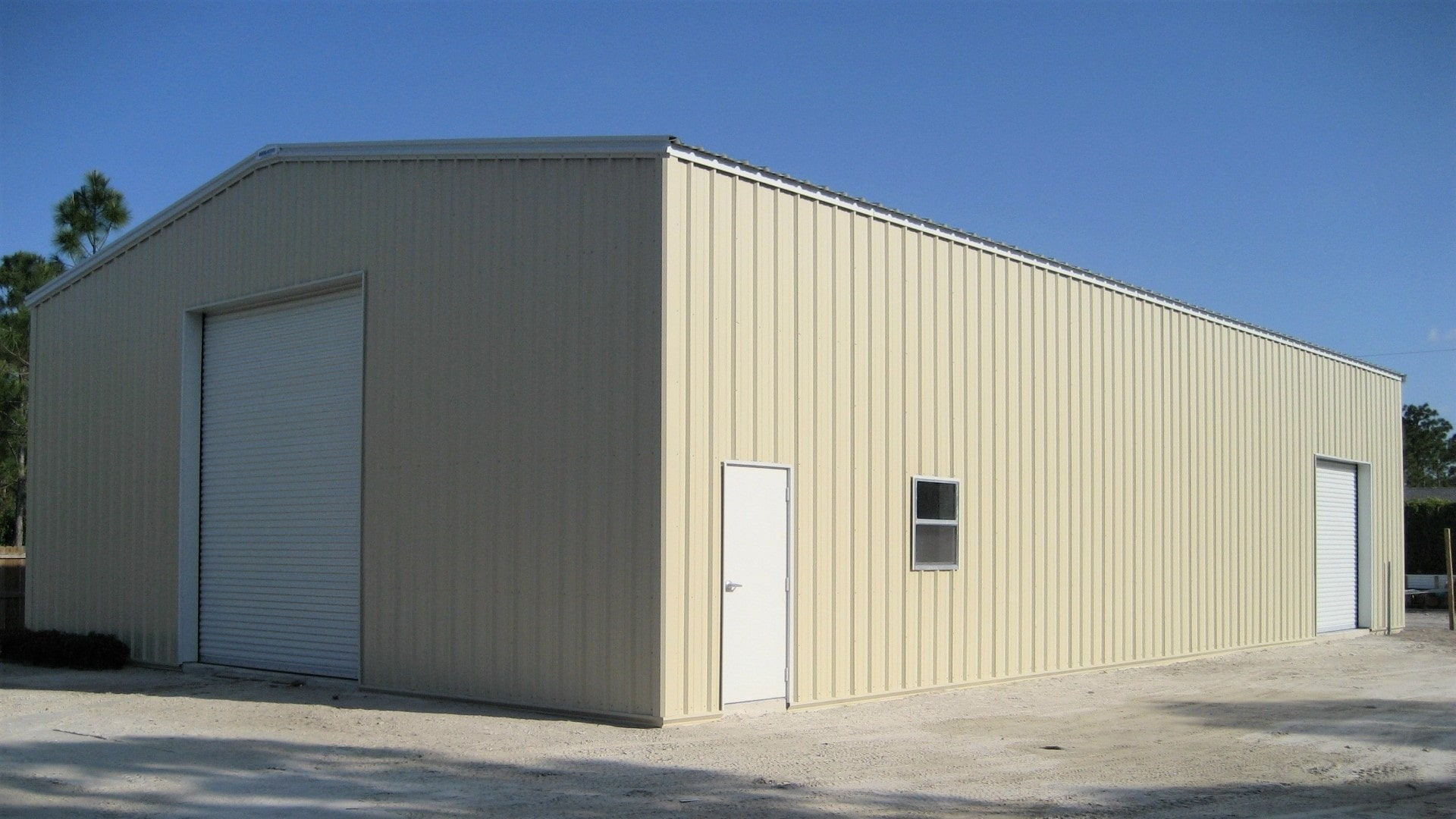 Tan metal garage shop with white trim, white walk door and white rollup door. View of left endwall and front sidewall.