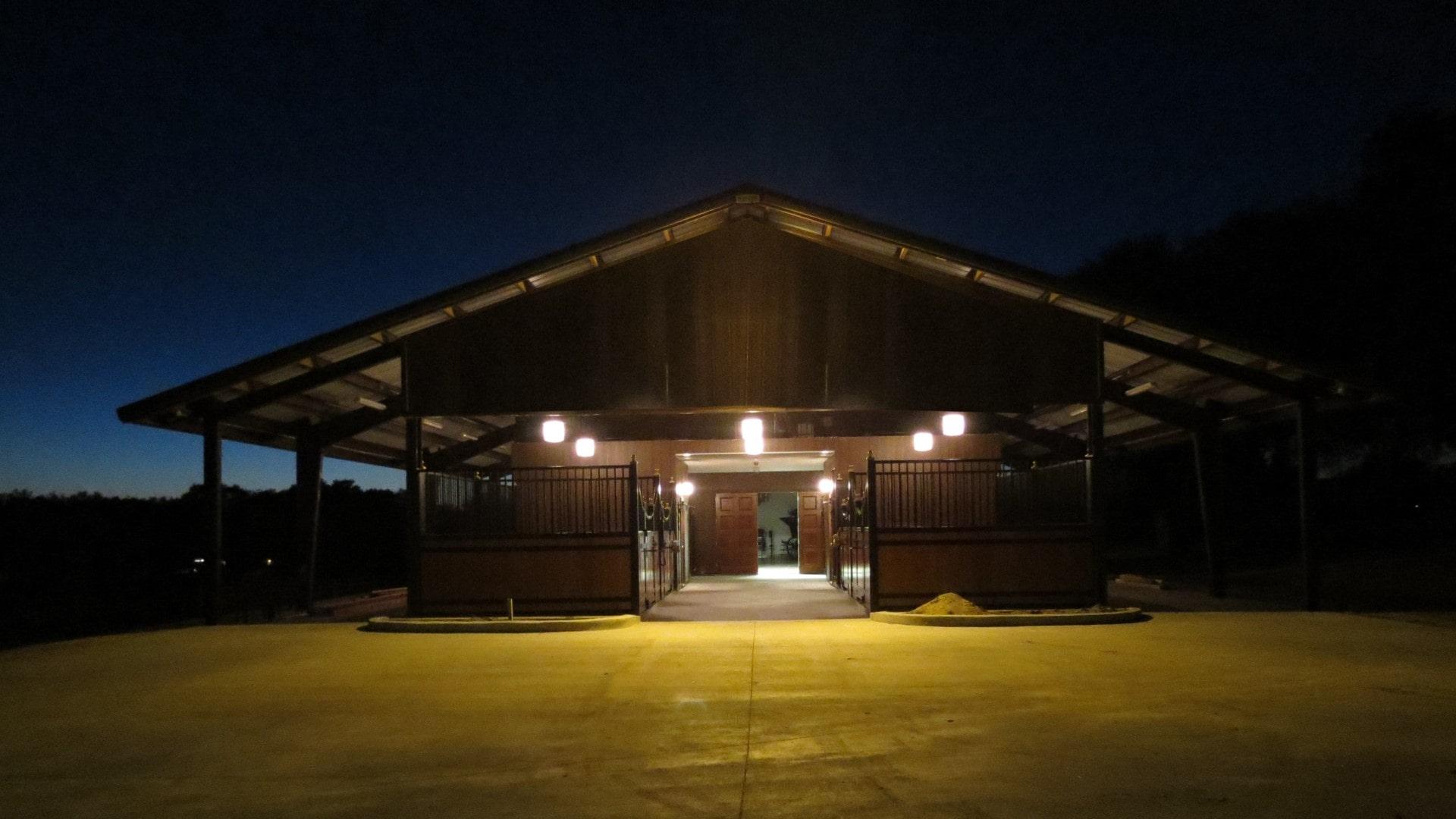 Custom horse barn exterior view of stalls at night with decorative lighting illuminating custom stalls.