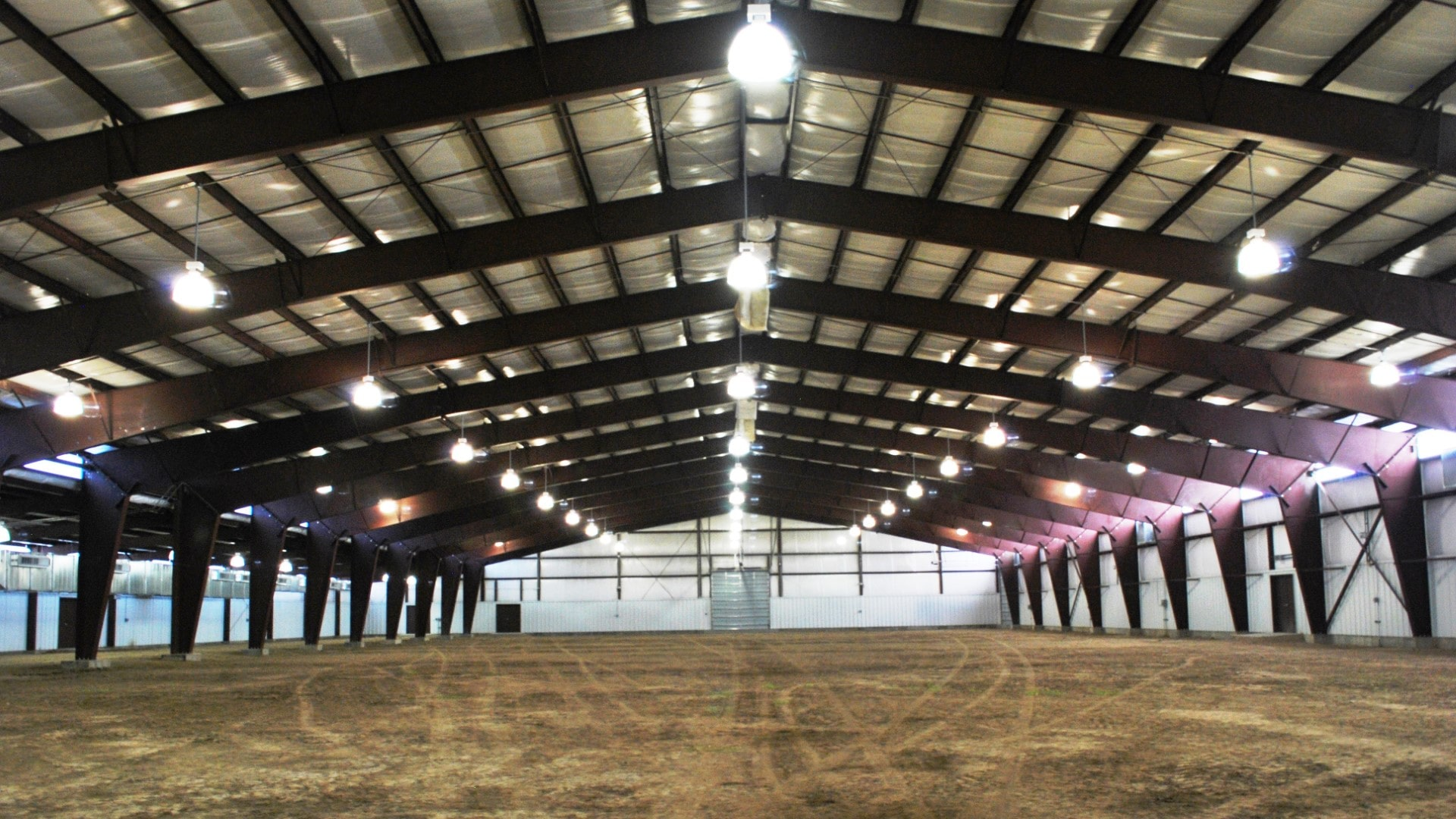 Colorado Fairgrounds clearspan steel riding arena indoor view looking down the length of arena.