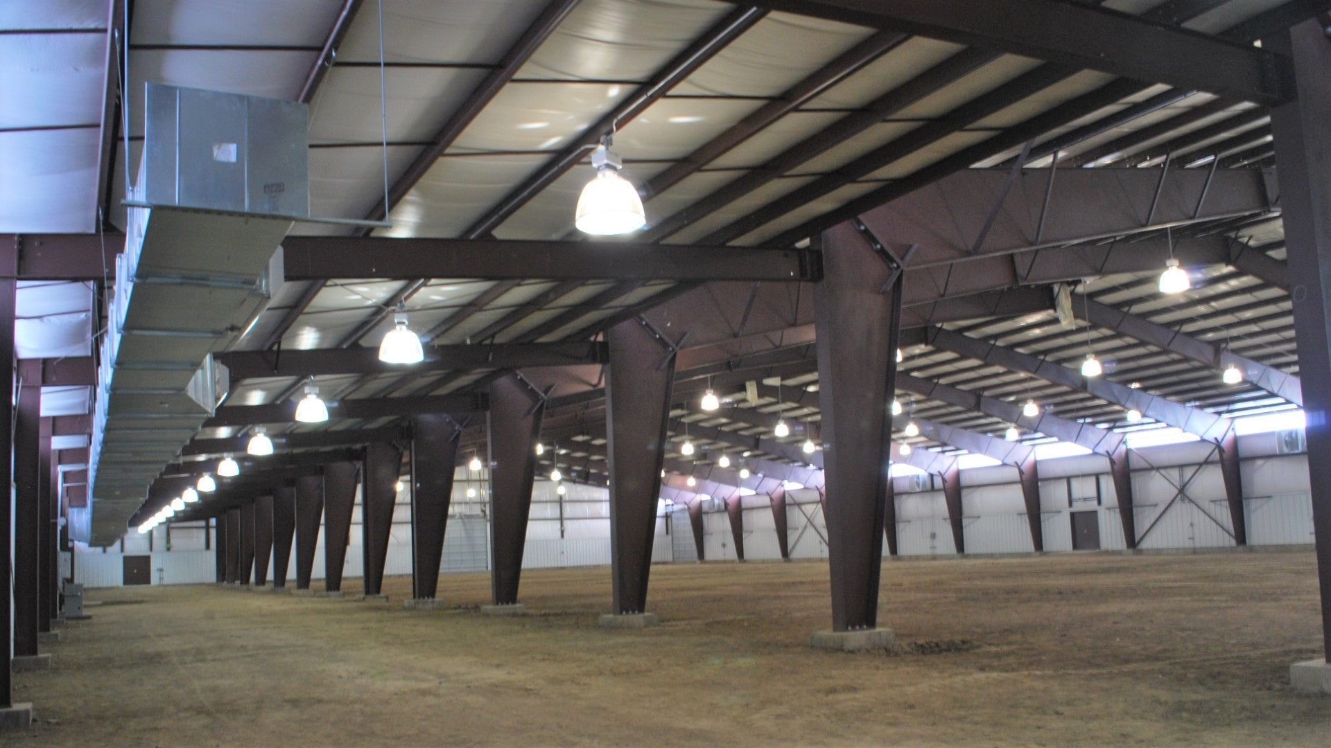 Colorado Fairgrounds steel riding arena indoor view of open leanto frame connecting to main building framelines.