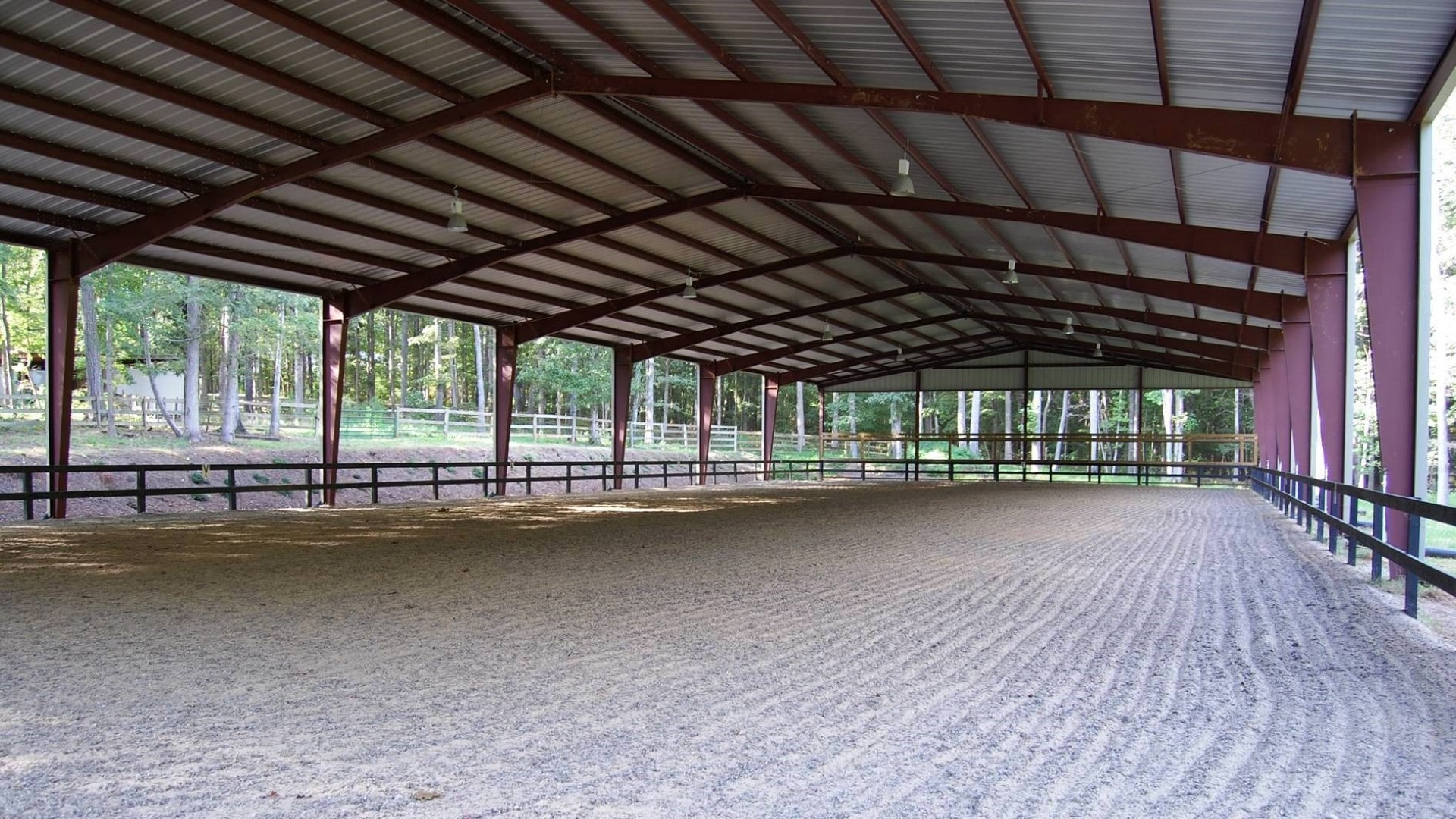Open outdoor metal riding arena with partially sheeted gable ends.