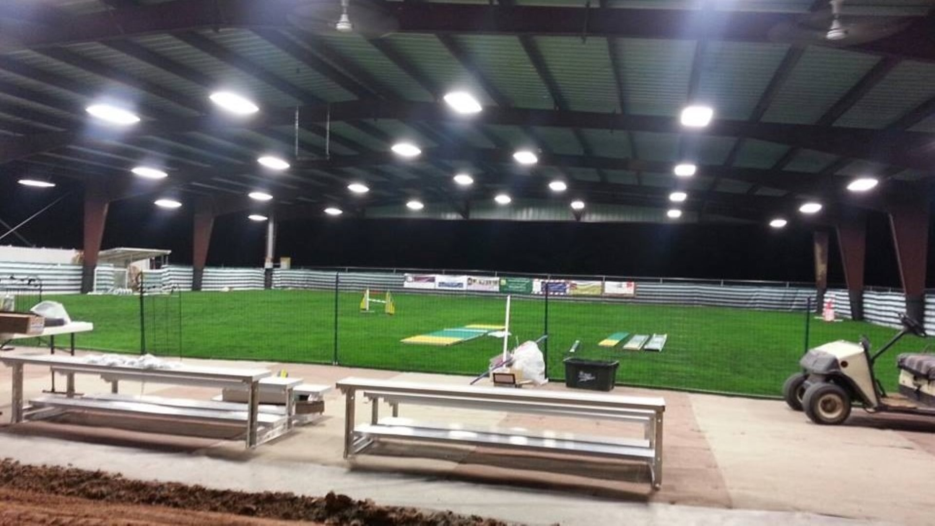 Open roof only metal building with partially sheeted gable ends at night with commercial lighting illuminating artificial turf.