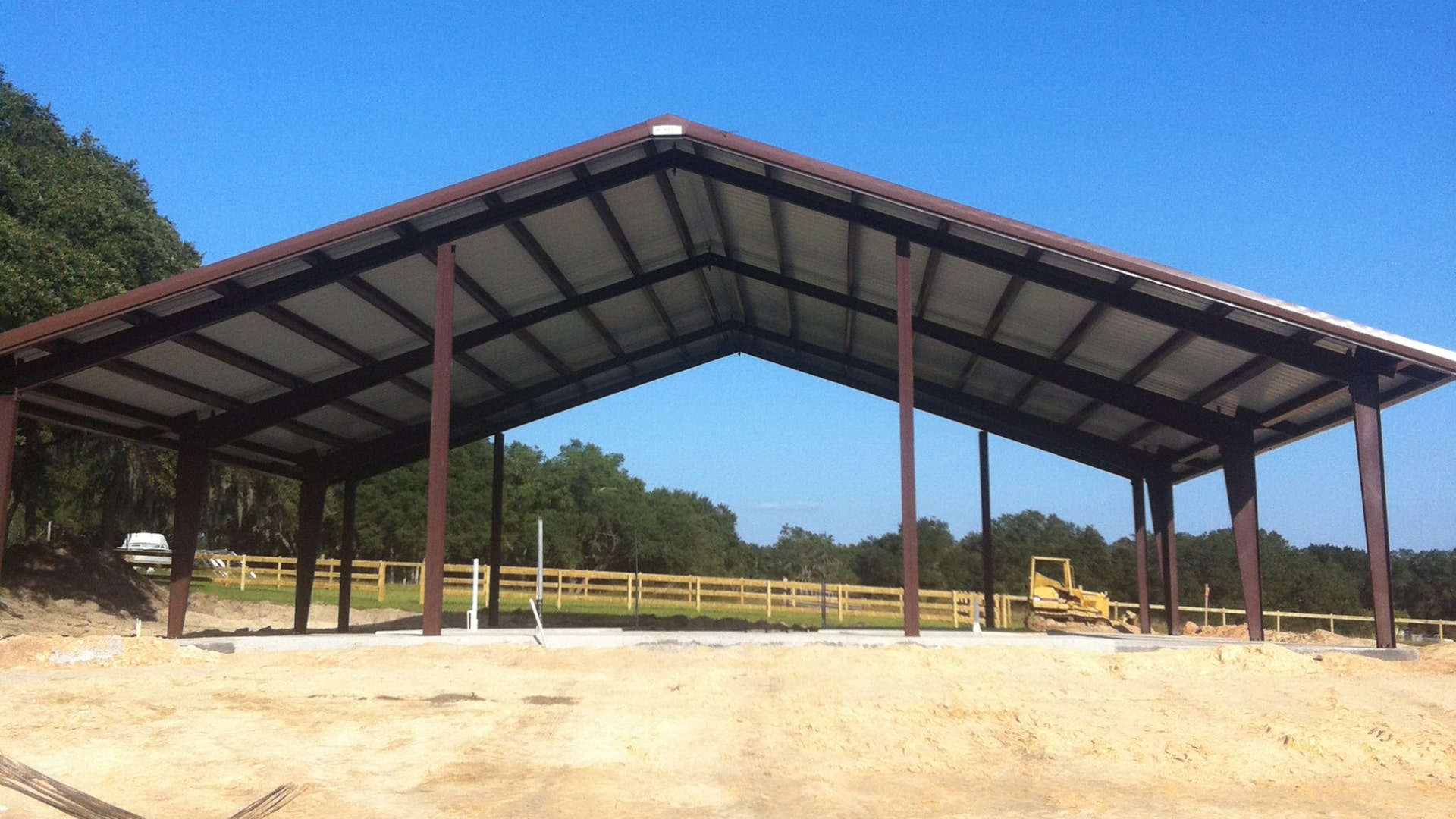 Simple open steel riding arena with steeper roof pitch and brown trim.