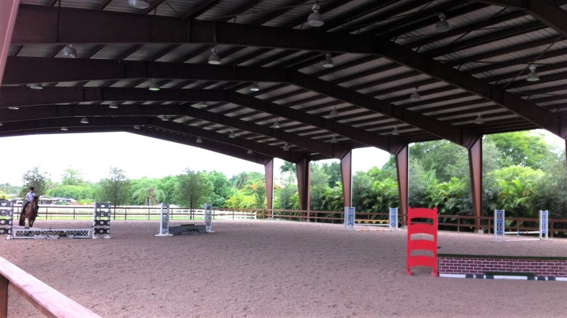 Open steel riding arena with custom lighting and half-load endwall frames with no columns.