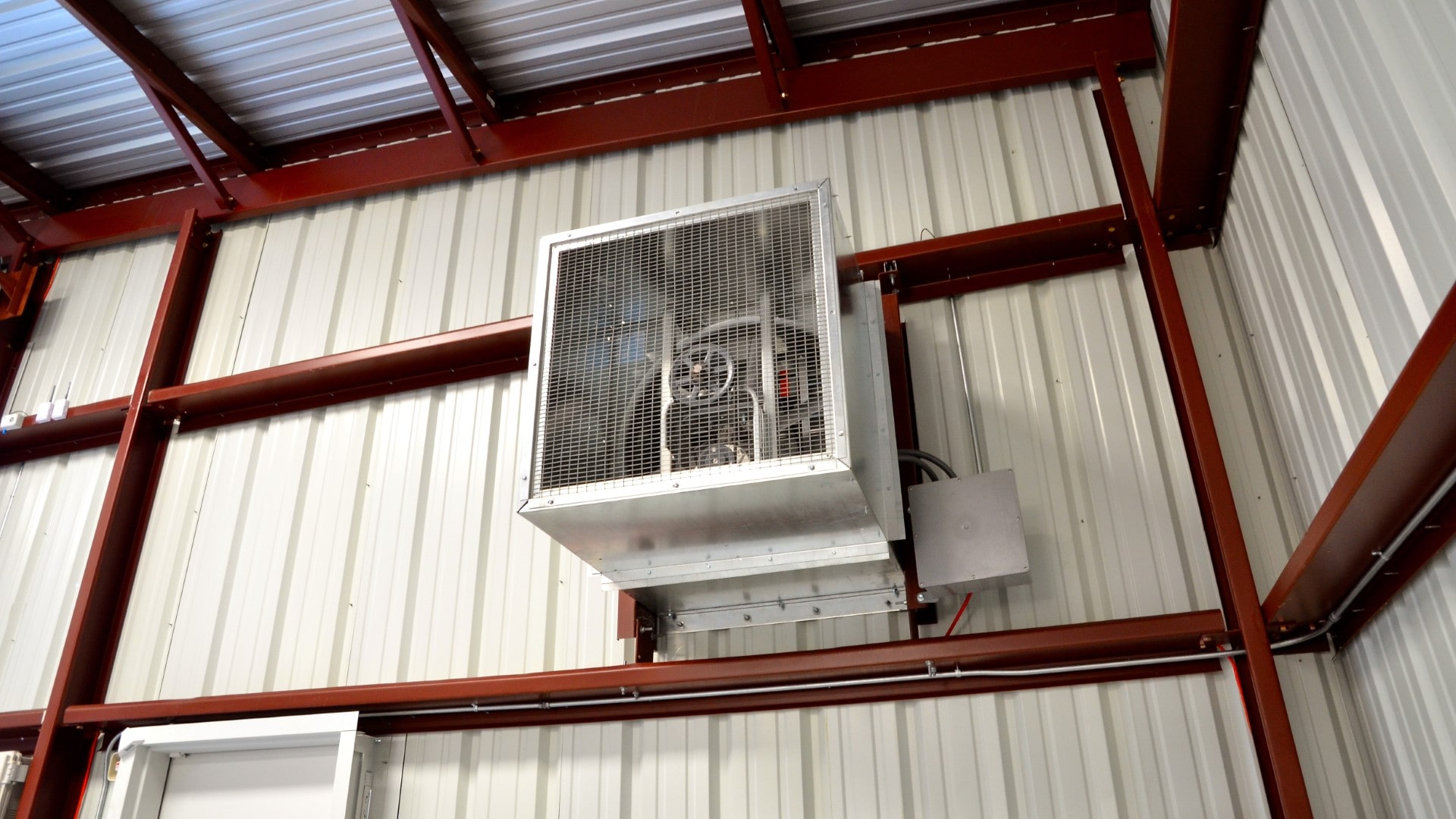 A metal building with exhaust fan, view from inside.